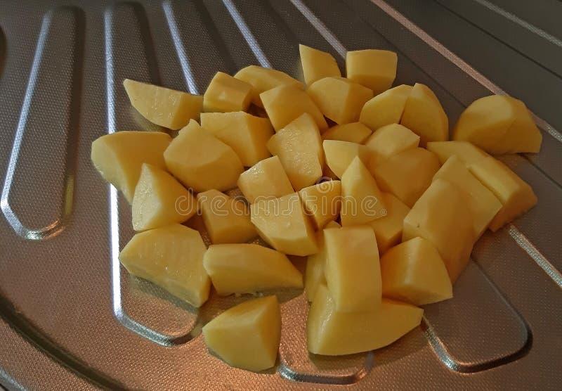 Le patate incidono le fette nella cucina fotografia stock