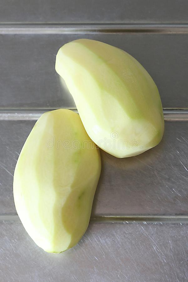 Le patate sbucciate e aspettano per essere cucinate fotografie stock libere da diritti