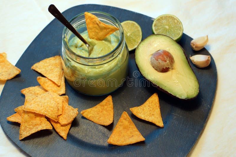 Le patatine fritte ed il guacamole triangolari dei nacho sauce dalla calce e dall'aglio dell'avocado fotografie stock libere da diritti