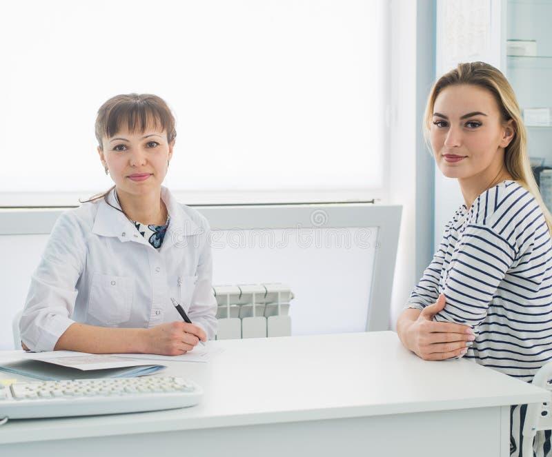 Le patient de sourire recevant une consultation médicale et regardant l'appareil-photo, le docteur féminin s'assied au bureau sur photo libre de droits