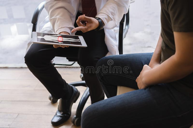 Le patient masculin de docteur et de cancer du testicule discutent au sujet du rapport des essais de cancer du testicule Cance de photographie stock