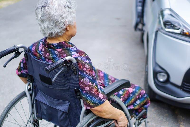 Le patient supérieur ou plus âgé asiatique de femme de dame s'asseyant sur le fauteuil roulant pour préparer obtiennent à sa voit photos libres de droits
