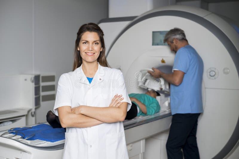 Le patienten för doktor With Colleague Preparing för CT-bildläsning fotografering för bildbyråer