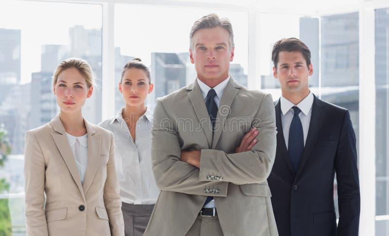 Le patron avec ses bras a plié la position avec les collègues sérieux derrière image libre de droits