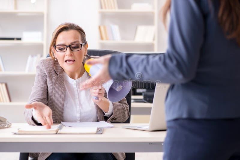 Le patron fâché écartant l'employé pour la mauvaise contre - performance images stock