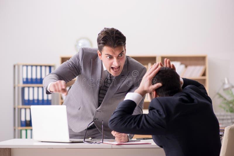 Le patron fâché criant à son employé photographie stock libre de droits
