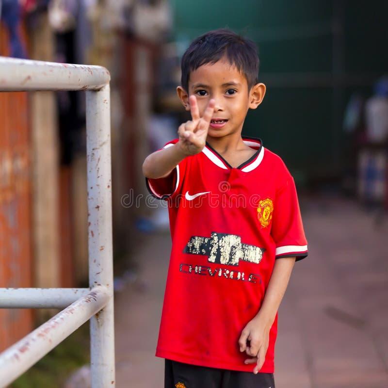 Le pauvre garçon cambodgien montre le signe de victoire photos stock