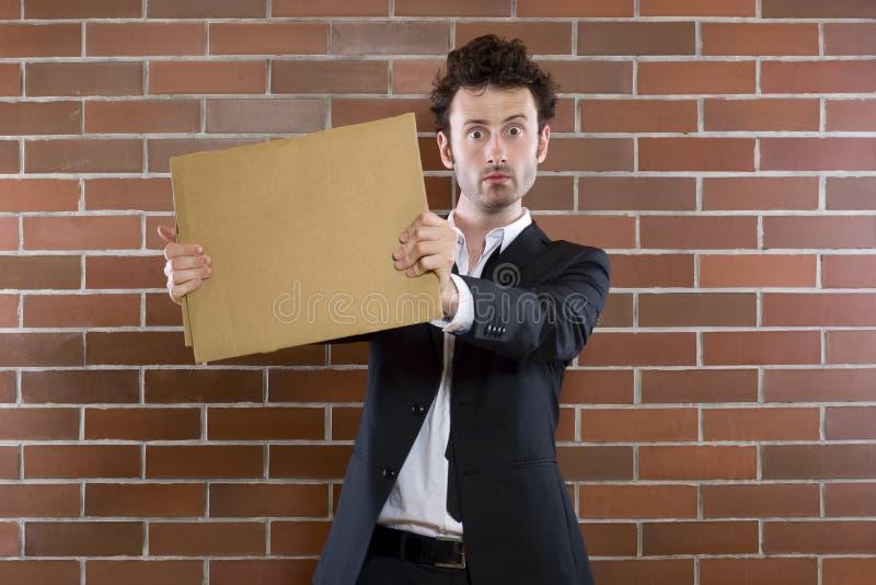 Le pauvre homme d'affaires unshaved parle en faveur avec un signe blanc images libres de droits