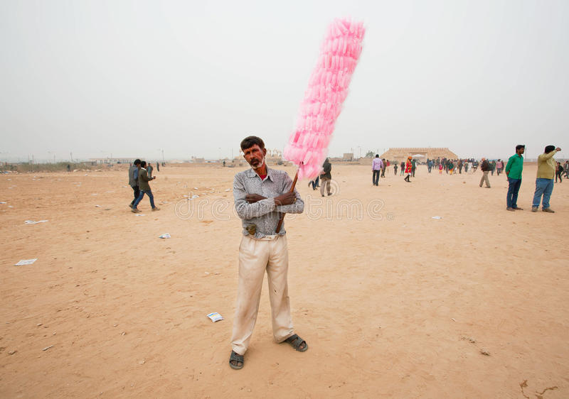 Le pauvre vendeur seul de la sucrerie de coton se tient dans le désert image stock