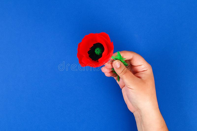 Le pavot rouge Anzac Day, souvenir de papier de Diy, se rappellent, papier de cr?pe de Jour du Souvenir sur le fond bleu photo libre de droits