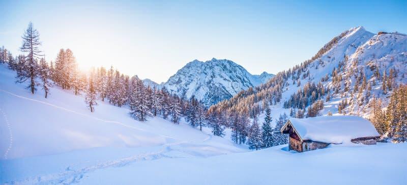 Le pays des merveilles d'hiver dans les Alpes avec le chalet de montagne au coucher du soleil photographie stock libre de droits