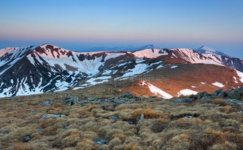 Le paysage du lac dans le gel aux hautes montagnes et aux champs couverts de neige Ciel avec des nuages Jour de source ensoleillé images stock