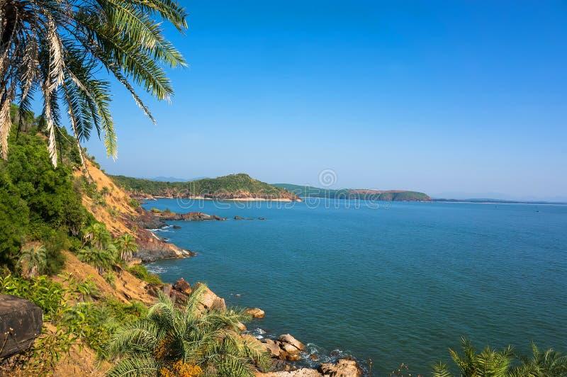 Le paysage est belle côte rocheuse avec le palmier, la mer bleue et le ciel sans nuages en plage de l'OM, Karnataka, Inde images stock