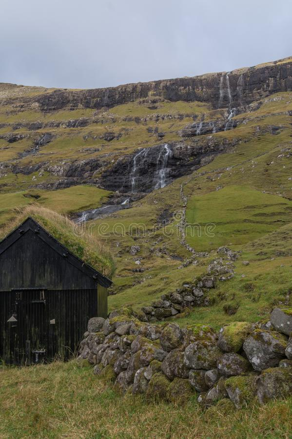 Le paysage féroïen typique avec la carlingue en bois, monopolisent la parole, et cascade, les Iles Féroé, Danemark images libres de droits