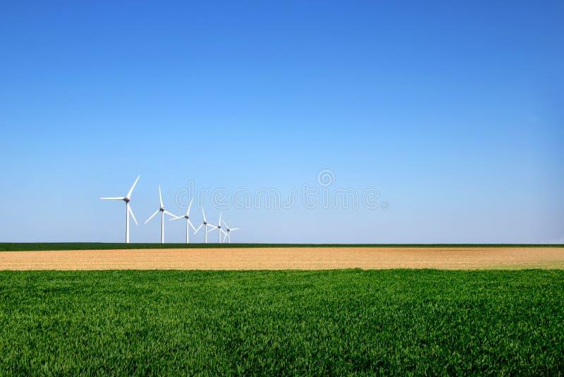 Le paysage moderne graphique des turbines de vent a aligné dans un domaine images stock