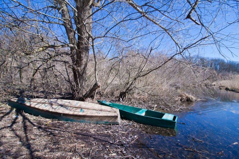 Le paysage tôt de ressort avec de petits vieux bateaux de pêche selfmade en bois donnent un coup de volée et les arbres nus su image libre de droits