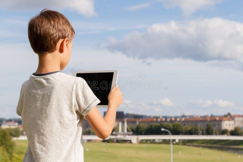 Le PC för pojkehållminnestavla utomhus- Bakgrund för blå himmel och stads Dra tillbaka till skolan, utbildning som lär, teknologi royaltyfria bilder