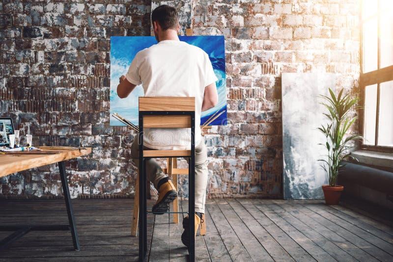 Le peintre masculin s'assied sur la chaise dans la photo de toile avant et de dessin dans le studio Classe et atelier d'art Procé photos libres de droits