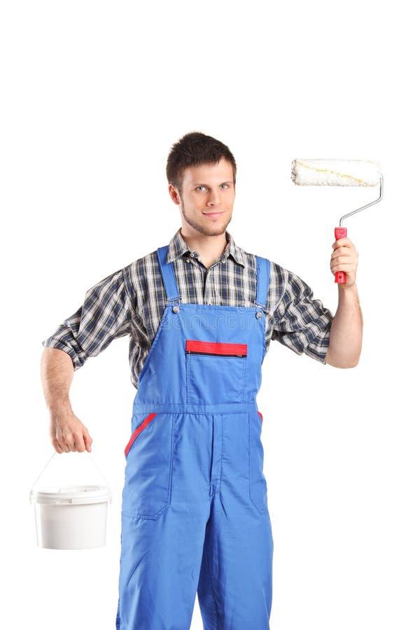 Le peintre masculin trouant un rouleau de peinture et la couleur bucket images stock