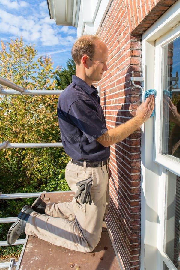 Le peintre néerlandais sur l'échafaudage nettoie le châssis de fenêtre avec le tissu photo libre de droits