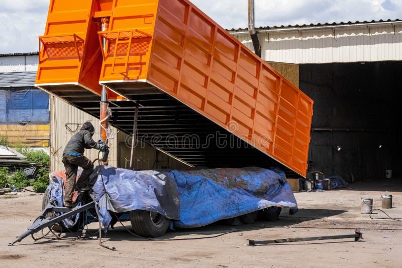 Le peintre peint le corps de la remorque du transporteur de grain dans la couleur orange du pistolet de pulvérisation photos libres de droits