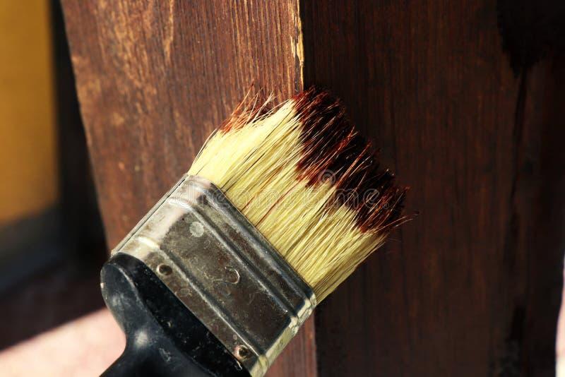 Le peintre qui conseil en bois de peinture avec la petite brosse photo stock