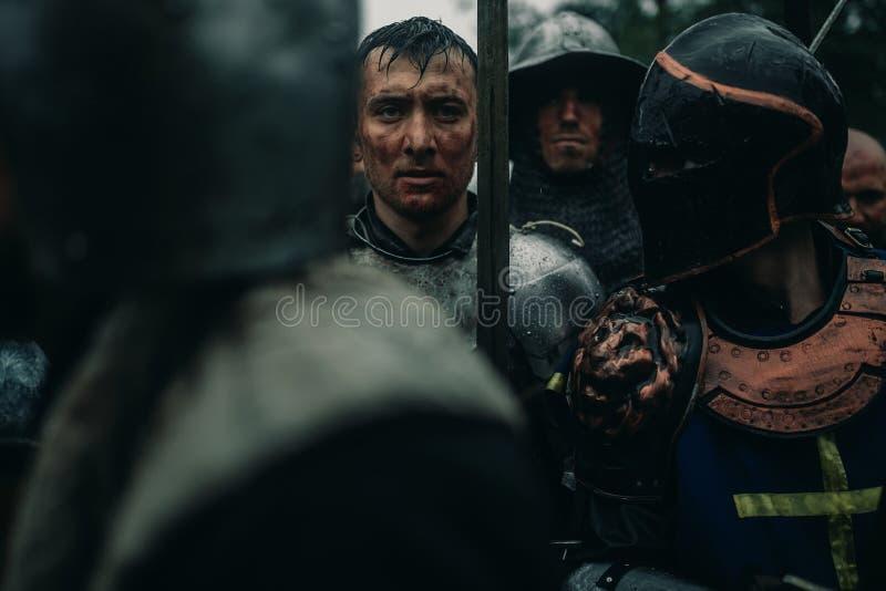 Le peloton des chevaliers m?di?vaux des crois?s se tiennent dans les armures et les casques images stock