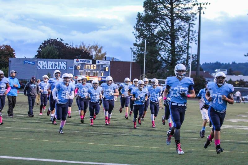Le peloton du football de garçons fonctionne sur le champ avec les chaussettes roses pour soutenir la conscience de cancer du sei images libres de droits