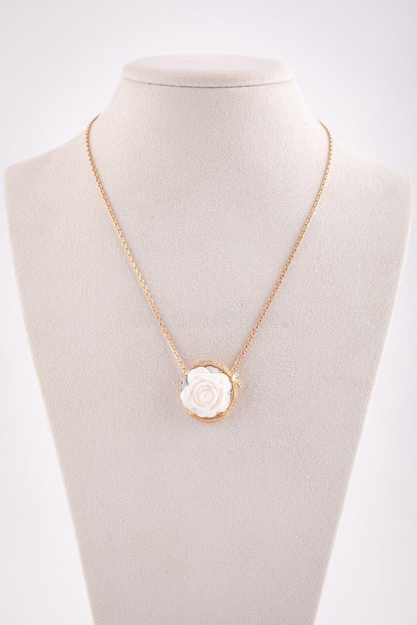 Le pendant des femmes d'or sous forme d'anneau et de roses de la pierre blanche sur la chaîne d'or d'isolement sur le fond blanc photos libres de droits