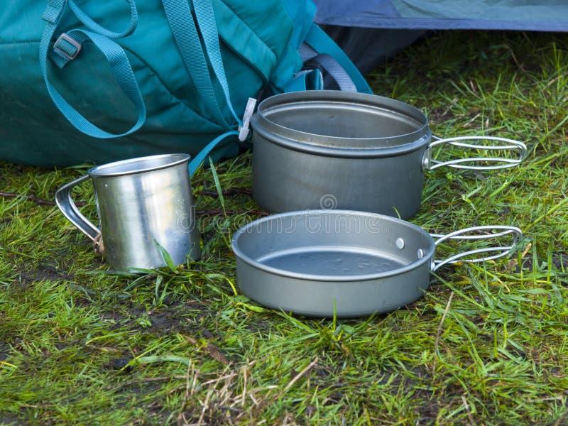 Le pentole per il campeggio sono sull'erba sui precedenti di una parte posteriore fotografia stock