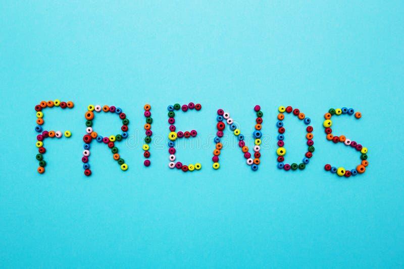 Le perle multicolori dei bambini, sparse su un fondo blu, la parola fotografia stock