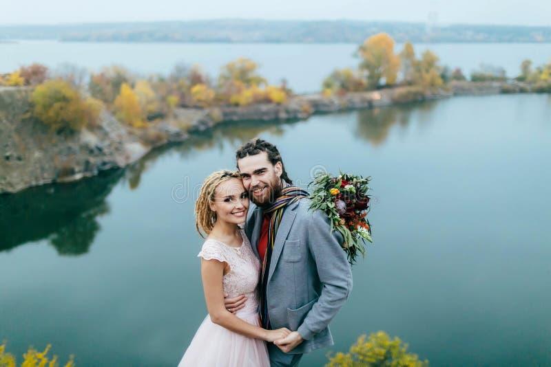 Le persone appena sposate alla moda delle coppie stanno posando prima di un lago sulla collina Cerimonia di nozze di autunno all' fotografia stock