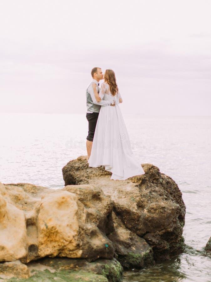 Le persone appena sposate bacianti che stanno sulla scogliera ai precedenti del mare immagine stock libera da diritti