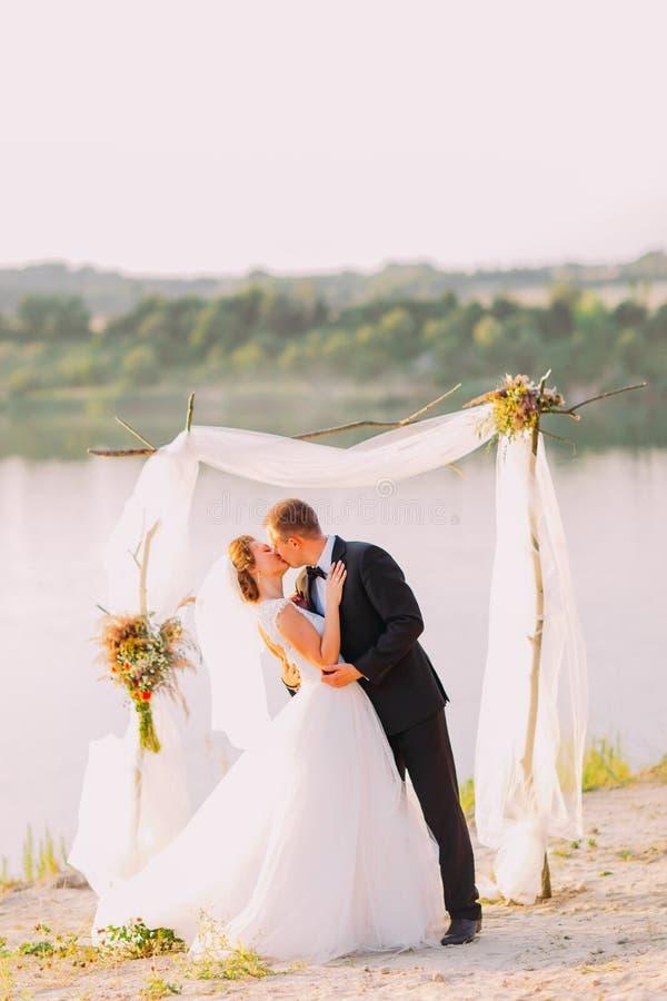 Le persone appena sposate bacianti happpy durante la cerimonia di nozze vicino al fiume fotografia stock libera da diritti