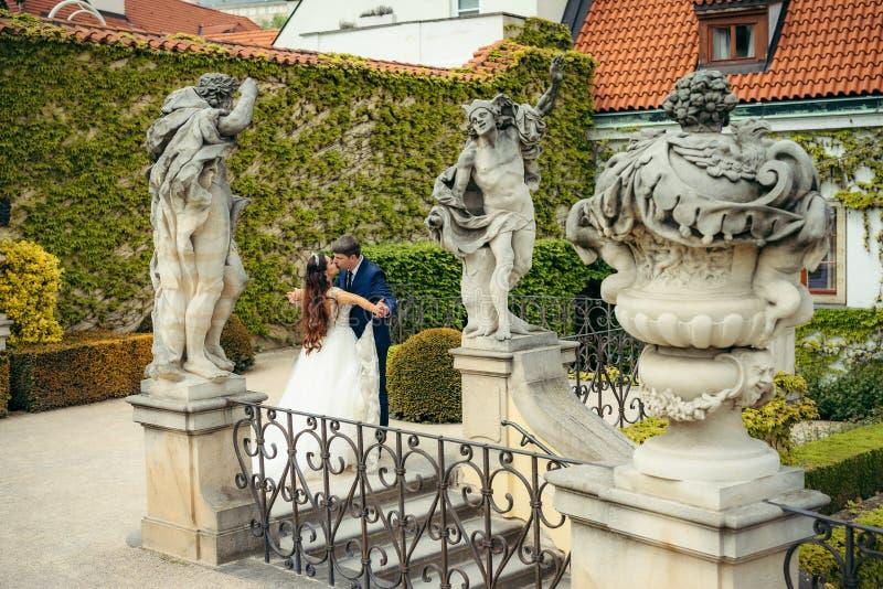 Le persone appena sposate bacianti sensibili stanno spendendo il tempo nel giardino decorato con i monumenti Posizione di Praga immagini stock libere da diritti