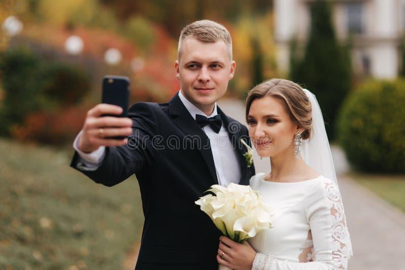 Le persone appena sposate fanno un selfie sullo smartphone in autunno fotografia stock libera da diritti