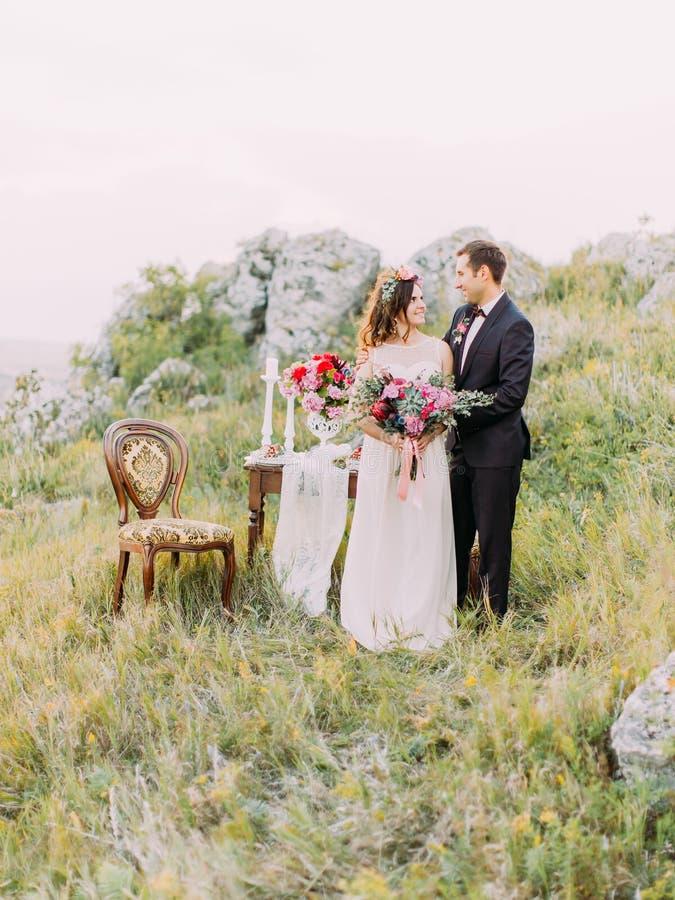 Le persone appena sposate sorridenti che stanno vicino alla tavola hanno messo nelle montagne fotografia stock libera da diritti