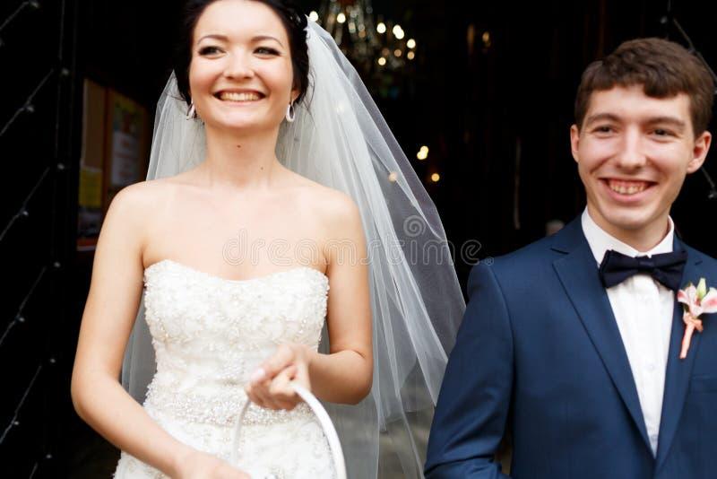 Le persone appena sposate sorridenti stanno nella parte anteriore della chiesa fotografie stock libere da diritti