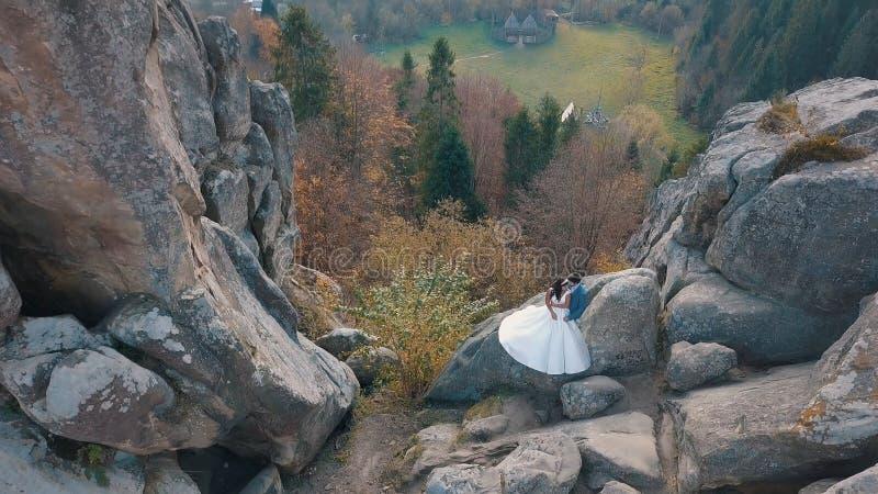 Le persone appena sposate stanno su un alto pendio della montagna Sposo e sposa Vista di Arial fotografie stock libere da diritti