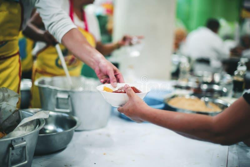 Le persone che tengono in mano un piatto ricevono una donazione da un buon amico, il concetto di dare con cura immagine stock