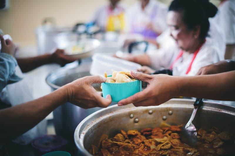 Le persone che tengono in mano un piatto ricevono una donazione da un buon amico, il concetto di dare con cura immagini stock