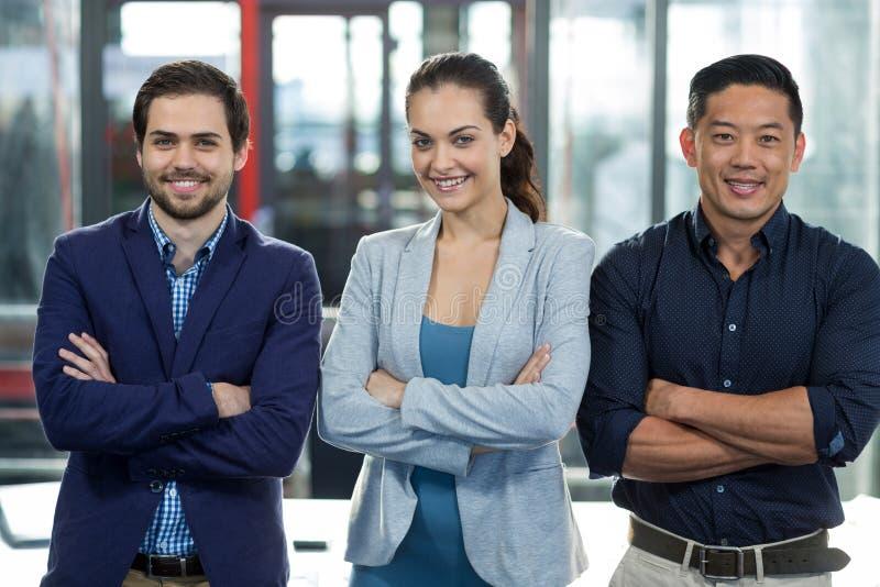 Le persone di affari sorridenti che stanno con le armi hanno attraversato in ufficio immagini stock