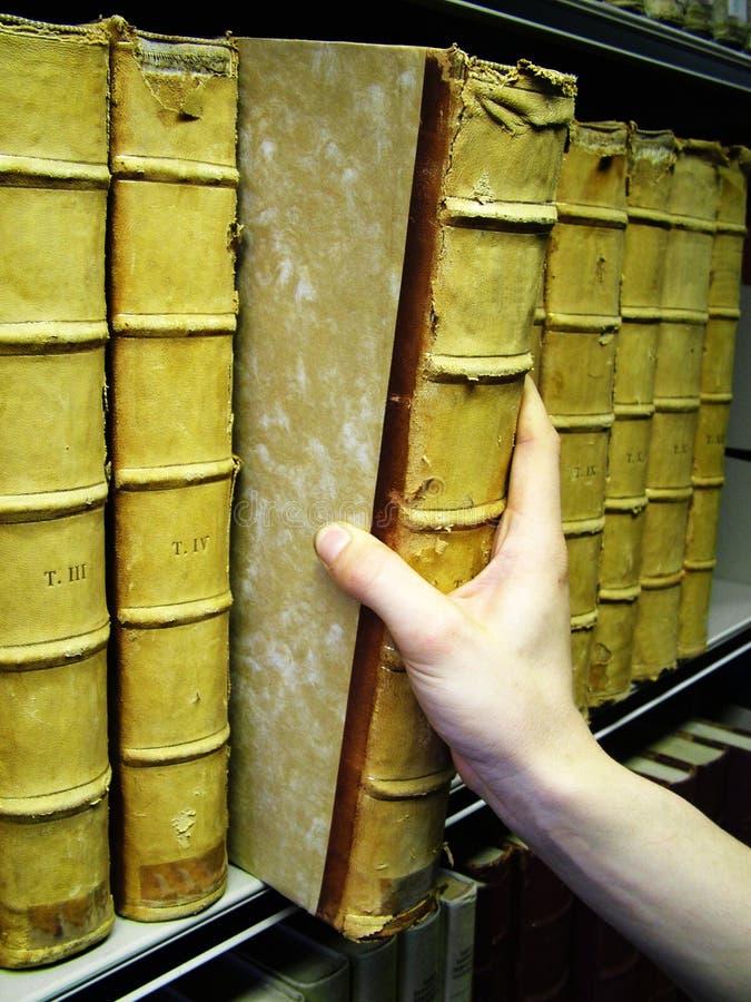 Le persone passano la rimozione del libro vecchio dallo scaffale per libri immagine stock