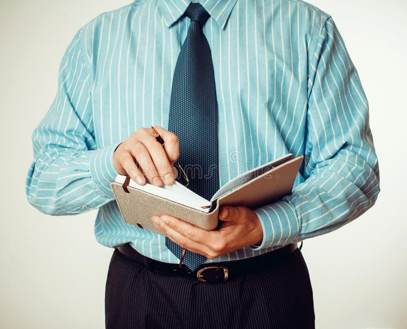 Le personnel administratif écrit des notes dans l'agenda photographie stock libre de droits