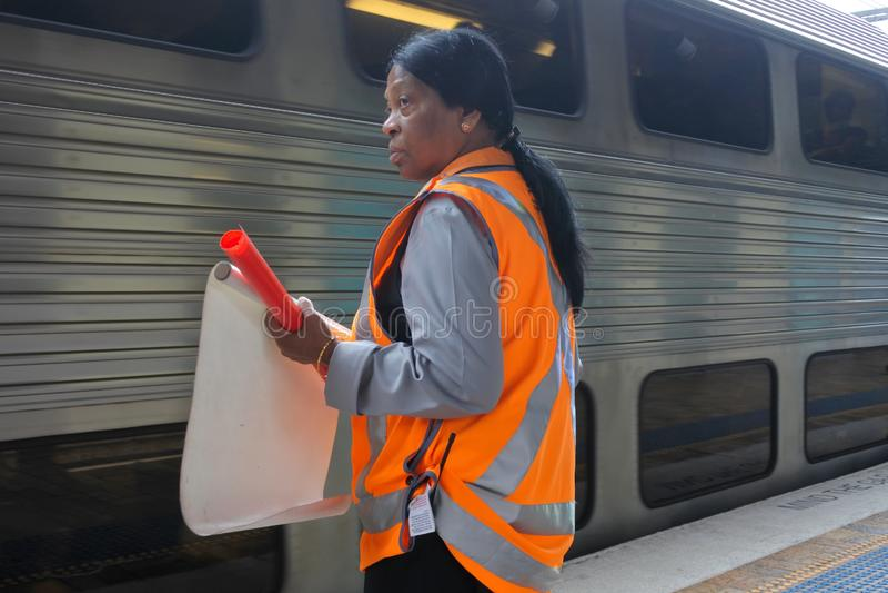 Le personnel de station ondule le drapeau blanc de départ à la garde d'un train de attente en station de Sydney Central Railway photo libre de droits