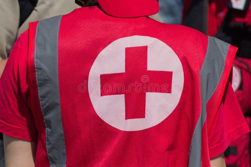 Le personnel médical dans l'uniforme avec le signe de la Croix-Rouge fournit l'aide médicale photographie stock libre de droits