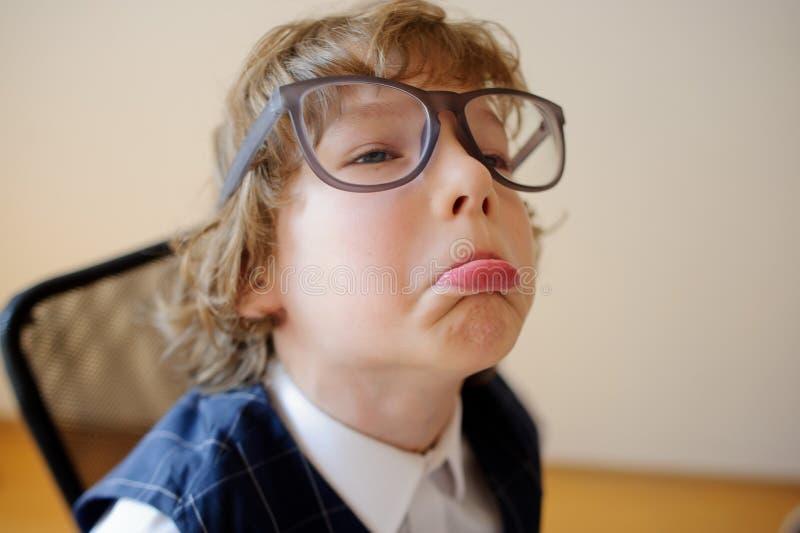 Le petit écolier ridicule en verres énormes font des visages images stock