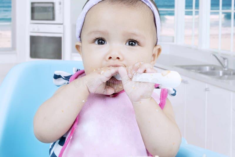 Le petit bébé apprend à manger du gruau photos libres de droits