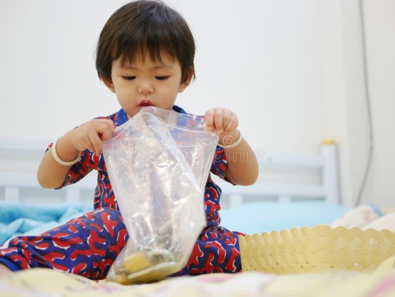 Le petit bébé asiatique apprenant à ouvrir une fermeture éclair en plastique mettent en sac seule photo libre de droits