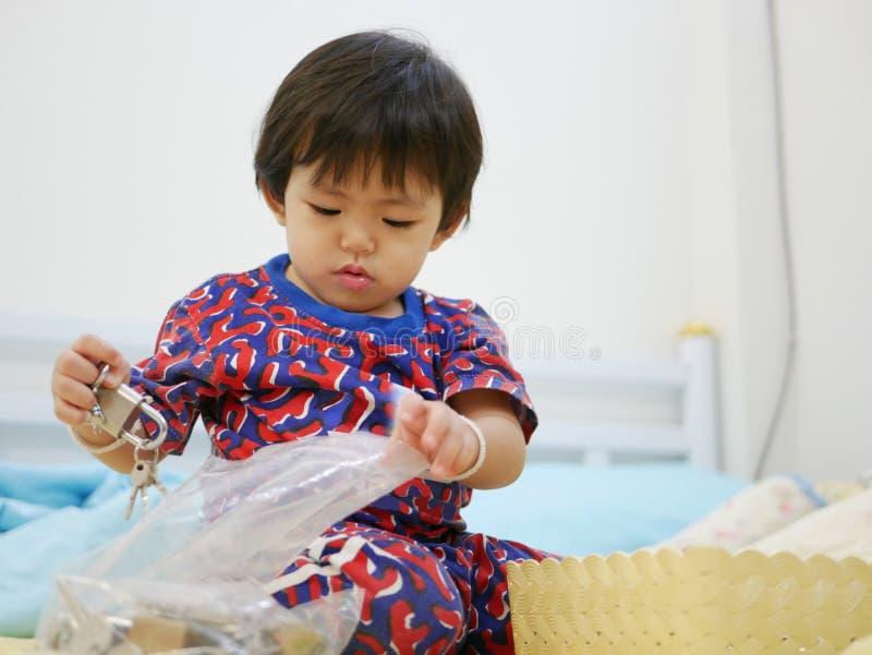 Le petit bébé asiatique essayant de mettre des clés dans une fermeture éclair en plastique mettent en sac photographie stock